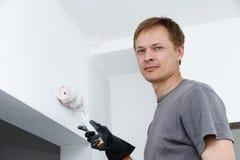 Mannen målar en vägg med en rulle Arkivbild