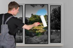 Mannen målar tillbaka en fönsterfärg med en målarfärgrulle Royaltyfri Fotografi