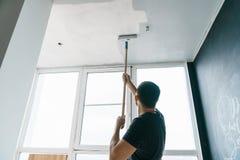 Mannen målar väggarna, och taket i grå färger färgar och att stå med hans baksida till kameran Fokus på rullen Arkivbild