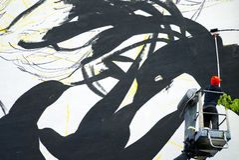 Mannen målar väggen på den mobila elevatorn royaltyfria bilder