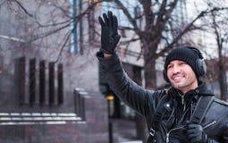 Mannen mötte en vän i gatan i vinter och vinkade till honom Han lyssnar till musik till och med hörlurar Arkivbild