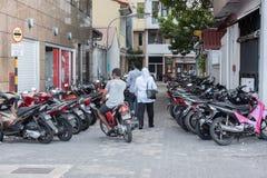 MANNEN MALDIVERNA - FEBRUARI, 13 2016 - folk i gatan för afton ber tid Arkivfoton