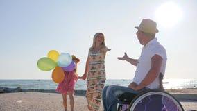 Mannen, mamman och dottern för realitet som inaktiverade den rörelsehindrade hoppar med ballonger i panelljus-, liten flicka- och stock video