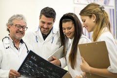 Mannen manipulerar att se röntgenstrålen medan attraktiva kvinnligsjuksköterskor royaltyfria bilder