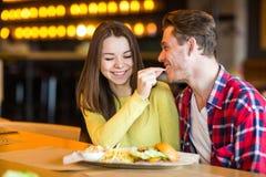 Mannen matar kvinnan i kafé arkivfoto