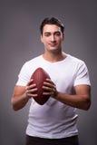 Mannen med amerikansk fotboll i sportbegrepp arkivfoto