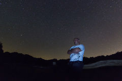 Mannen med armar korsade anseende mot stjärnklar natt Polstjärnanstjärna för stjärnklar natt, Ursa Major, Karlavagnenkonstellatio Royaltyfri Fotografi