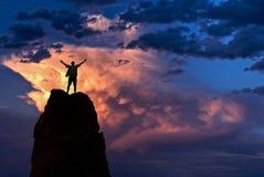 Mannen med armar lyftte i begreppet för himmelvinnareframgång arkivbild