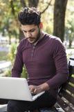 Mannen med bärbara datorn på sommar parkerar på ljus dag royaltyfri fotografi