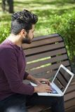 Mannen med bärbara datorn på sommar parkerar på ljus dag arkivbild