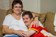 Mannen med besegrar syndromkramar hans äldre syster On en soffa arkivfoton