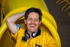 Mannen med besegrar syndromskratt och spelar på en lekplatsglidbana Royaltyfria Bilder