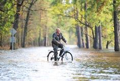 Mannen med cykeln går på den översvämmade vägen Royaltyfria Foton