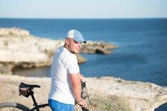 Mannen med cykeln på kusten Royaltyfria Foton