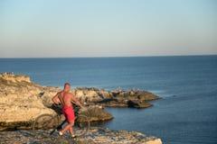 Mannen med cykeln på kusten Royaltyfri Bild