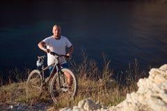 Mannen med cykeln på kusten Royaltyfri Fotografi