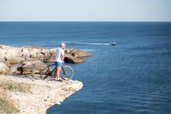 Mannen med cykeln på kusten Arkivbild