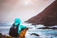Mannen med en hund som är främst av lantligt kustlinjelandskap med berg och vågor och solen, rays att komma till och med molnen Arkivbilder
