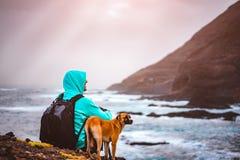 Mannen med en hund som är främst av lantligt kustlinjelandskap med berg och vågor och solen, rays att komma till och med molnen Arkivbild