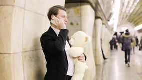 Mannen med en leksakbjörn kallar hans älskling lager videofilmer