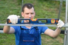 Mannen med en nivå för att mäta lutningen kontrollerar designen, närbild royaltyfria bilder