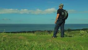 Mannen med en ryggsäck bak hans baksida står på kanten av berget och beundrar sikten av sjön skytte lager videofilmer