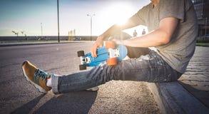 Mannen med en skateboard sitter Fotografering för Bildbyråer