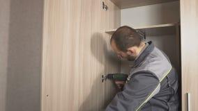 Mannen med en skruvmejsel monterar möblemang stock video