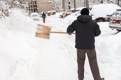 Mannen med en skyffel gör ren snö från vägen royaltyfri foto