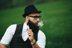 Mannen med ett skägg röker den elektroniska cigaretten Royaltyfri Foto