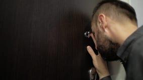 Mannen med ett skägg ser i kikhålet lager videofilmer