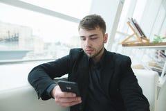 Mannen med ett skägg ser smartphonen under ett avbrott för lunch i ett kafé Kaffeavbrott i ett stilfullt ljust kafé Royaltyfria Bilder