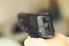 Mannen med ett vapen som är klart att skjuta - fokusera på den tillbaka delen av vapnet arkivfoto