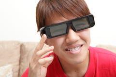 Mannen med exponeringsglas 3D ler den hållande ögonen på filmen 3D Royaltyfri Bild