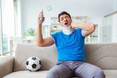 Mannen med fotboll för fotboll för halsskada hållande ögonen på hemma Royaltyfri Bild