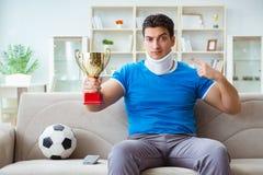 Mannen med fotboll för fotboll för halsskada hållande ögonen på hemma Arkivbilder