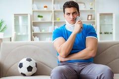 Mannen med fotboll för fotboll för halsskada hållande ögonen på hemma Royaltyfri Foto