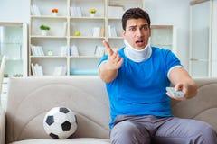Mannen med fotboll för fotboll för halsskada hållande ögonen på hemma Fotografering för Bildbyråer