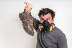 Mannen med gasmasken rymmer den smutsiga stinky skon Arkivbild