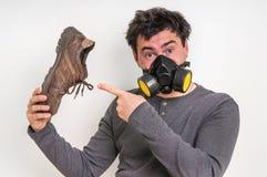 Mannen med gasmasken rymmer den smutsiga stinky skon Arkivfoton