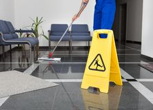 Mannen med golvmopp och blöter golvtecknet Royaltyfri Foto