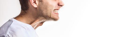 Mannen med grep hårt om tänder på vit bakgrund som är ilsken grinar, tandvärk på vit bakgrund royaltyfri bild