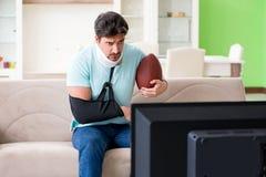 Mannen med hals- och armskada som håller ögonen på amerikansk fotboll på tv arkivbilder
