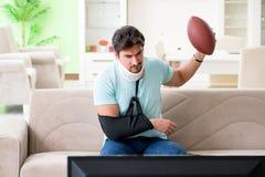 Mannen med hals- och armskada som håller ögonen på amerikansk fotboll på tv royaltyfri fotografi