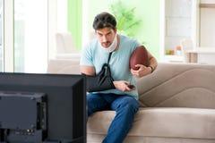 Mannen med hals- och armskada som håller ögonen på amerikansk fotboll på tv royaltyfria foton
