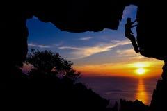 Mannen med kameraklättring vaggar i grottan Fotografering för Bildbyråer