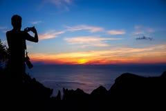 Mannen med kameraklättring vaggar på berget Arkivfoton