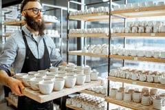Mannen med keramik på krukmakerit shoppar arkivbild
