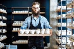 Mannen med keramik på krukmakerit shoppar royaltyfri bild