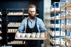 Mannen med keramik på krukmakerit shoppar arkivfoto